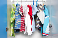 Children clothes in wardrobe royalty free stock images