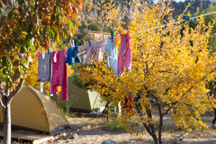 Children Clothing hanging on rope for drying after washing. In sunny country garden background stock photo