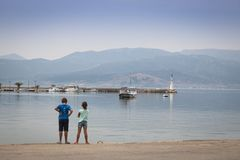 Children at the coast of Nafplio, Greece. NAFPLIO, GREECE - SEPTEMBER 2017: Children at the pier of the ancient city Nafplio in Greece Royalty Free Stock Image