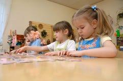 Children collect puzzles. Gadjievo, Russia - March 03, 2011: Children collect puzzles Stock Photography