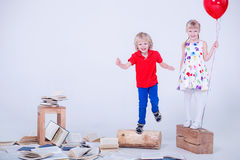 Children with colored balloons. The photo was taken in a white studio. Lot of books are lying on the floor. Stock Photo