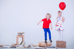 Children with colored balloons. The photo was taken in a white studio. Lot of books are lying on the floor. Royalty Free Stock Photo
