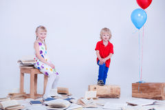 Children with colored balloons. The photo was taken in a white studio. Lot of books are lying on the floor. Royalty Free Stock Image