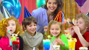 Children in colorful hats celebrating birthday with mother and fiends. Brother and sister in colorful hats celebrating their birthday with mother and fiends at stock video