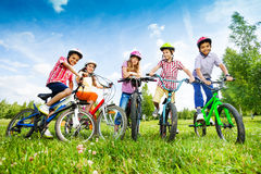 Children in colorful helmets hold their bikes. Children in colorful helmets hold bike handle-bars and are ready to ride their bikes in green field stock image