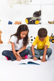 Children coloring. Two young african american children coloring in with crayons on their bedroom floor Stock Image