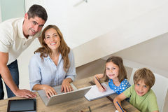Children coloring while parents using laptop Stock Photography