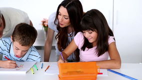 Children colouring with their parents stock video