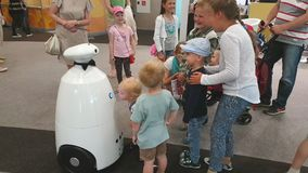 Children communicate with a robot at an exhibition stock footage
