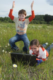 Children and computer in the meadow with daisies. Children in a meadow outdoors looking at a laptop computer Stock Photography