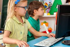 Children computer class us for education and video game. Children computer class for education and video game. Girl won boy in logical computer game sitting Stock Photography