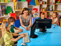 Children computer class us for education and video game. Boys and girls in children`s club developing computer games. New technologies alternative to classical Royalty Free Stock Photography