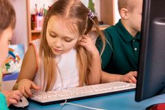 Children computer class us for education and video game. Boys and girls in children`s club who spend many hours behind computer monitor harmful to health Royalty Free Stock Photos