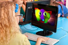 Children computer class us for education and video game. Kids in children`s club developing computer games. New technologies alternative to classical training Stock Images