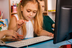 Children computer class us for education and video game. Children play on computer. Girl learns to type on keyboard Royalty Free Stock Photo