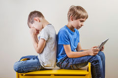 Children with computer. One boy using tablet and other kid rubbing tired eyes after long time playing game. Children with computer at home. One boy using tablet Stock Image