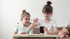 Children conduct a chemical experiment and are surprised by the chemical reaction. two little girls playing at home in. Children conduct chemical experiments at stock video