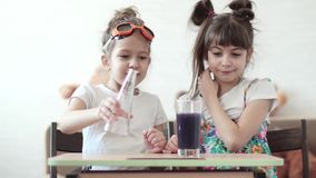 Chemical experiment at home. Children mix chemical elements and are surprised by the flowing reaction. Children conduct chemical experiments at home. two little stock footage