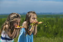 Children with confetti in hand inflate them in the wind Royalty Free Stock Images