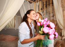 Children congratulate mother give her bouquet of flowers. Children congratulate mother give her a bouquet of flowers and a kiss, happy mother`s family day Stock Images