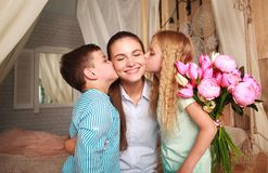 Children congratulate mother give her bouquet of flowers Stock Image