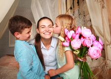 Children congratulate mother give her bouquet of flowers Stock Photo