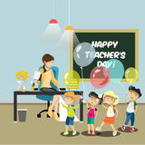 Children congratulate the teacher in the classroom. Children give flowers to the teacher Royalty Free Stock Images