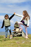 Children conquering mountain. Brother and sister on a mountain top, enjoying their feat Royalty Free Stock Photo