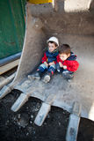 Children on construction site. Sitting in a large excavator bucket Royalty Free Stock Photography