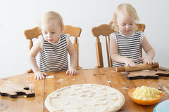 Children cook. Children enthusiastically help in the kitchen to cook Royalty Free Stock Photos