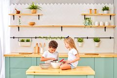 Children are cooked and played with flour and dough in the kitchen stock image