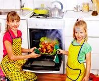 Children cooking chicken at kitchen. Stock Photo