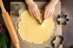 Children cooking Christmas cookies, cut the dough with cookie cutter, family traditions, delicious sweet holiday food. Children is cooking Christmas cookies, cut royalty free stock images