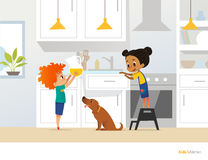 Children cooking food in kitchen. Red head boy holding pitcher with drink, girl in apron standing by stove and cute pet dog. Home Stock Photos