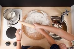 Children cooking. Kids rolling dough for cookies in toy kitchen. Above view Stock Photo