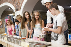 Children cooking pizza Royalty Free Stock Photos
