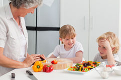 Children cooking with their grandmother. At home Royalty Free Stock Photos