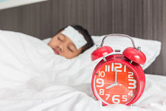 Children with cool fever on forehead and sleeping on the bed. Children with white cool fever on forehead and sleeping on the bed, focus on red clock stock images