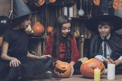 Children in costumes of fairy-tale characters for Halloween consider a pumpkin lamp. Children dressed in the costumes of fairy-tale monsters for a Halloween Stock Image
