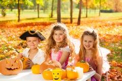 Children in costumes at Halloween craft pumpkin Stock Images