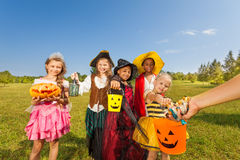 Children in costumes look at hand with sweets Stock Photo