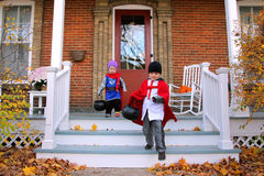 Children in Costumes Trick-or-Treating on Halloween. Two young American children dressed in knight costumes are trick-or-treating on Halloween stock photo