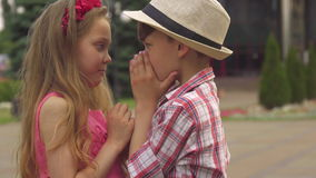 Children cover their mouthes with hands. Nice caucasian children covering their mouthes with hands outdoors. Close up of little brunette boy and his female stock footage