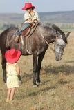 Children in cowboy hat riding horse outdoors. Two happy children in cowboy hats riding horse outdoors Stock Images