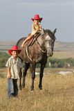 Children in cowboy hat riding horse outdoors Royalty Free Stock Photography