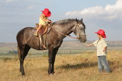 Children in cowboy hat riding horse outdoors Stock Image