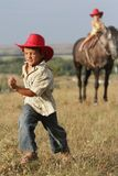 Children in cowboy hat riding horse outdoors royalty free stock photo