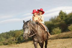 Children in cowboy hat riding horse outdoors Royalty Free Stock Images