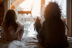 Children in cozy costumes on bed royalty free stock image