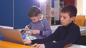 Children creating robots at school, stem education. Early development, diy, innovation, modern technology concept. Children creating robots at school, stem stock footage